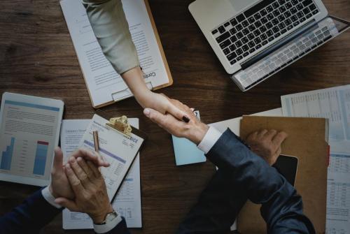 handshake-across-desk--two-business-people